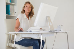 Casual businesswoman thinking at her desk Royalty Free Stock Photography