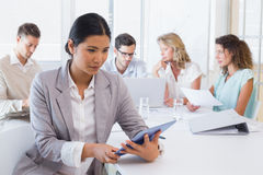 Casual businesswoman using her tablet during a meeting Stock Photography