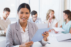 Casual businesswoman using her tablet during a meeting Stock Photos