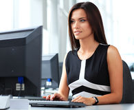 Casual businesswoman using laptop in office Stock Image