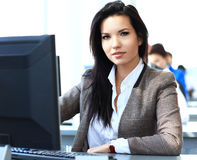Casual businesswoman using laptop in office Stock Photos