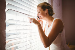 Casual businesswoman using mobile phone while looking through blinds Stock Photography