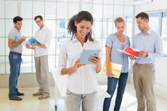 Casual businesswoman using tablet with team behind her Royalty Free Stock Photography