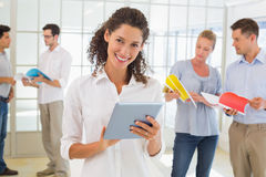 Casual businesswoman using tablet with team behind her Stock Photography