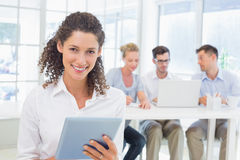 Casual businesswoman using tablet with team behind her Stock Photos
