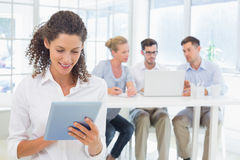 Casual businesswoman using tablet with team behind her Stock Images
