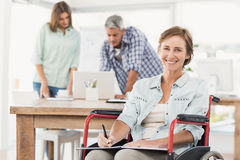 Casual businesswoman in wheelchair with notepad Royalty Free Stock Photos