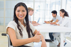 Casual businesswoman in wheelchair smiling at camera giving thumbs up Stock Photos