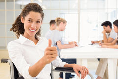 Casual businesswoman in wheelchair smiling at camera giving thumbs up Royalty Free Stock Photo