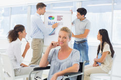 Casual businesswoman in wheelchair smiling at camera during presentation Stock Photography
