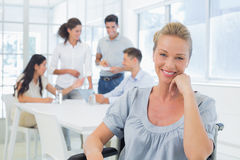 Casual businesswoman in wheelchair smiling at camera with team behind her Royalty Free Stock Images
