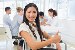 Casual businesswoman in wheelchair smiling at camera with team behind her Stock Photography