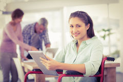 Casual businesswoman in wheelchair using tablet Royalty Free Stock Photos