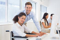 Casual businesswoman in wheelchair working at her desk with colleague Royalty Free Stock Image