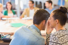 Casual businesswoman whispering secret to her colleague Royalty Free Stock Image