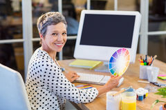 Casual businesswoman working with computer and colour chart Stock Photos