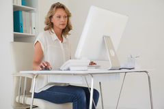 Casual businesswoman working at her desk Royalty Free Stock Photos
