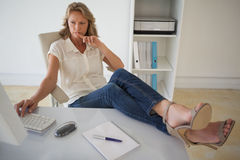 Casual businesswoman working with her feet up at desk Royalty Free Stock Image