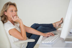 Casual businesswoman working with her feet up at desk Royalty Free Stock Photography