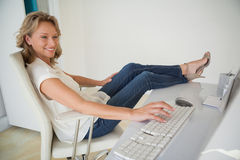 Casual businesswoman working with her feet up at desk Stock Photo
