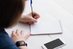 Casual businesswoman writing on notebooks Royalty Free Stock Images