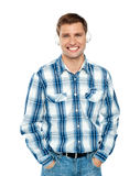 Casual caucasian guy listening to music. Through headphones posing with hands in pocket Stock Photography