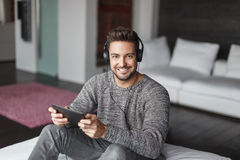 Casual caucasian man listening music indoor by tablet Stock Photography