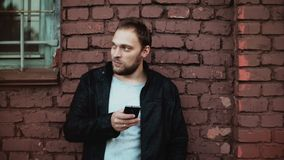 Casual Caucasian man using smartphone outside. Handsome bearded young male businessman texting. Red brick wall 4K. Confident businessman using mobile office stock footage