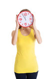 Casual caucasian woman holds clock on her face. Stock Photos