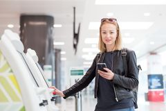 Casual caucasian woman using smart phone application and check-in machine at the airport getting the boarding pass. Royalty Free Stock Images