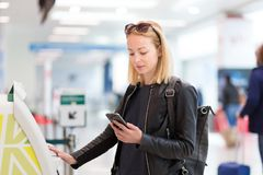 Casual caucasian woman using smart phone application and check-in machine at the airport getting the boarding pass. Royalty Free Stock Image