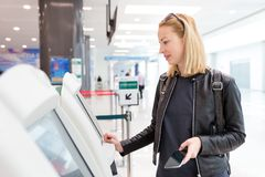 Casual caucasian woman using smart phone application and check-in machine at the airport getting the boarding pass. Stock Image