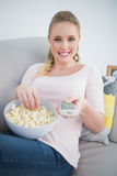 Casual cheerful blonde holding remote and lying on couch Royalty Free Stock Photos