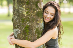 Casual cheerful brunette embracing a tree with closed eyes Royalty Free Stock Photos