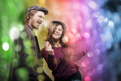 Casual cheerful couple dancing, colorful abstract background. Happy lovely young men and girl, wearing retro hats and casual clothes, dancing over blurred Royalty Free Stock Photography