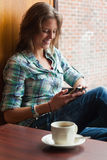 Casual cheerful student sitting next to window texting Stock Image