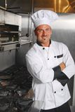 Casual chef. An attractive Caucasian chef leans casually against a stove in a commercial kitchen Stock Photo