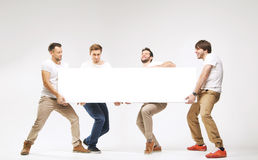 Casual clothed guys carrying huge billboard Stock Photos