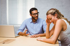 Casual colleagues in an argument at desk. Two casual business colleagues in an argument at office desk stock image
