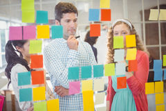 Casual colleagues looking at sticky notes on wall Stock Image