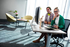 Casual colleagues smiling at camera. In the office stock photography