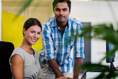 Casual colleagues smiling at camera. In the office stock image