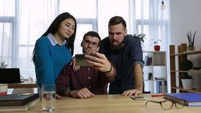 Casual colleagues taking self-portrait in office stock footage