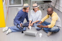 Casual colleagues using digital tablet on floor Stock Photos