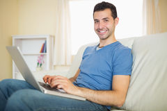 Casual content man sitting on couch using laptop looking at camera Stock Photo