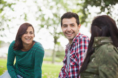 Casual content students sitting on the grass chatting Stock Images