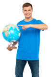 Casual cool guy pointing at rotating globe Royalty Free Stock Photography