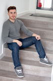 Casual cool man sitting on the stairs. At home Royalty Free Stock Photo