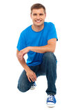 Casual cool young guy semi seated on floor Stock Photos