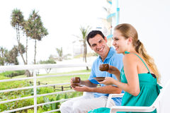 Casual couple. Young happy casual couple enjoying coffee on balcony with beautiful ocean view behind on holiday Royalty Free Stock Images